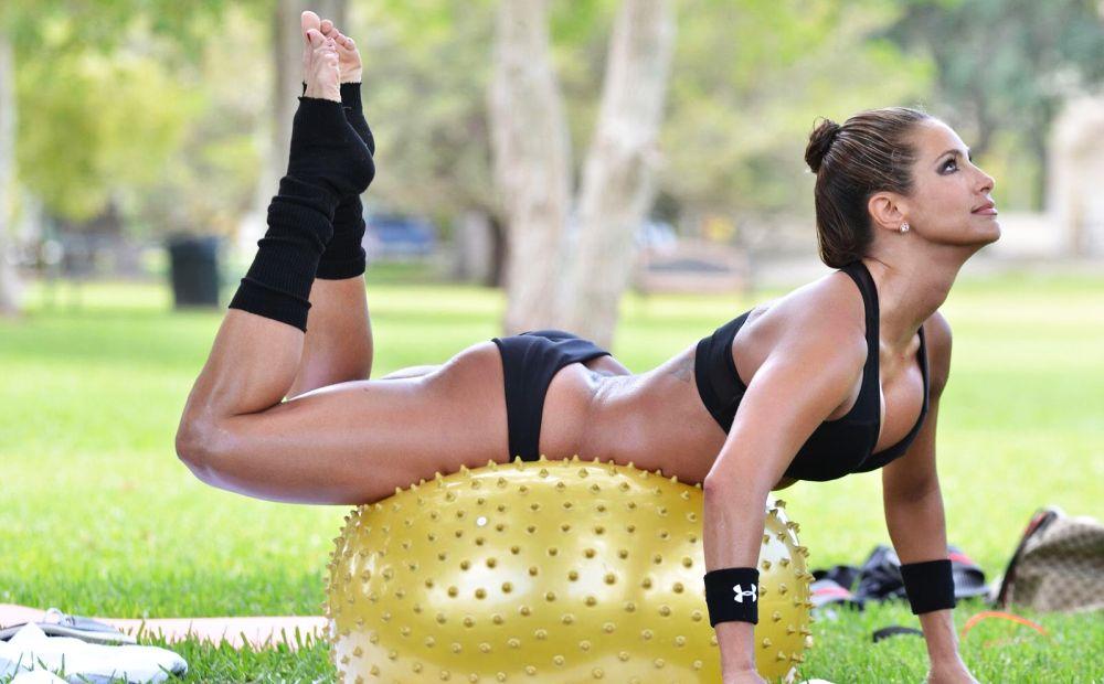 спортсменка делает упражнение на гимнастическом мяче